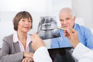 Dentist showing xray of teeth to elderly couple