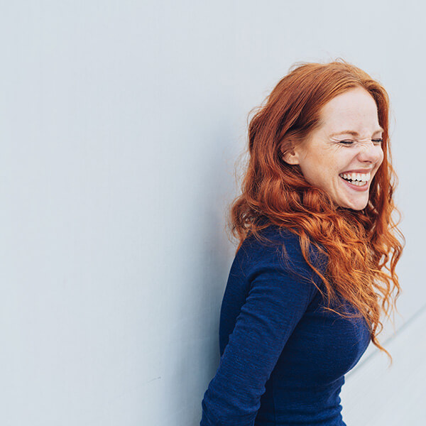 woman with red hair leans against a wall, laughing
